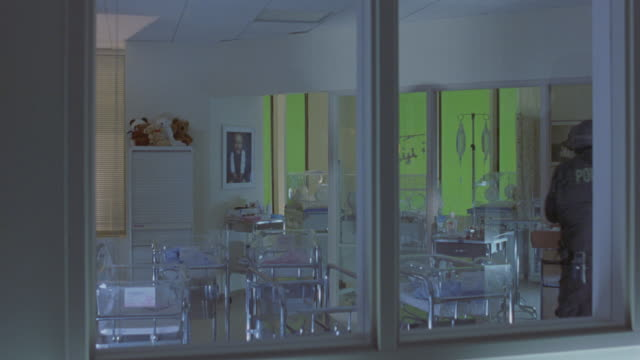 wide angle through window of swat team searching room in children's hospital. see men with rifles walk past glass or plastic chairs, incubators, and iv poles. room contains pictures of children and stuffed animal toys. see flashing lights move around wall - fire alarm stock videos & royalty-free footage