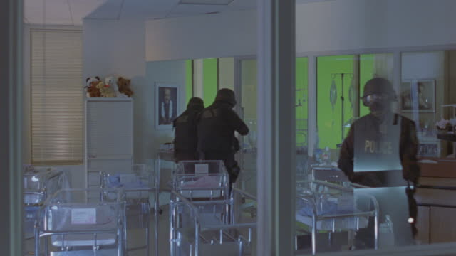 wide angle through window of swat team searching room in children's hospital. see men with rifles walk past glass or plastic chairs, incubators, and iv poles. room contains pictures of children and stuffed animal toys. see flashing lights move around wall - armed police forces stock videos & royalty-free footage