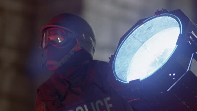 close angle of police officer wearing helmet, mask, and goggles next to search light. could be swat team member next to spotlight at stand-off. see sparks fly as glass light breaks and cop falls away. could be gunfire attack. police action. klieg light. - fly swat stock videos & royalty-free footage