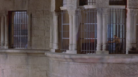 wide angle of armed guards searching prison interior. see guards with rifles and flashlights through iron prison bars. stone building contains columns along windows. could be mental institution. - iron bars for windows stock videos & royalty-free footage
