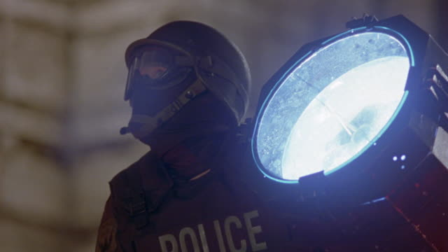 close angle of police officer wearing helmet, mask, and goggles next to search light. could be swat team member next to spotlight at stand-off. see sparks fly as glass light breaks and cop falls away. could be gunfire attack. police action. klieg lights. - fly swat stock videos & royalty-free footage