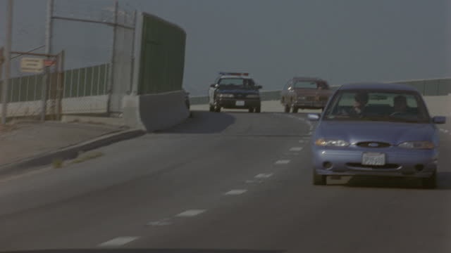 tracking shot of police car on overpass of three-lane freeway. see other cars, station wagons, and sedans drive past chain-link fences. could be part of car chase or police activity. cops. driving. highways. sfpd. - dolly shot stock videos & royalty-free footage