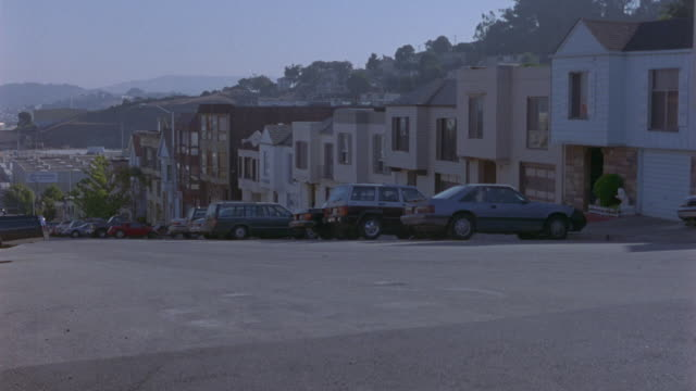 wide angle of police car driving uphill through residential area. see car pass sedans, pickup trucks, and station wagons parked in front of multi-story houses. buildings could be condominiums or townhouses. pan right as car turns at intersection and conti - in front of stock videos and b-roll footage