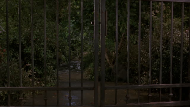 """pan up, medium down angle of dirt road to front gate entrance of """"central park"""" see bushes and trees behind fence. pans up to ball-shaped lights hanging from thatched ceiling of gazebo. - gazebo stock videos and b-roll footage"""