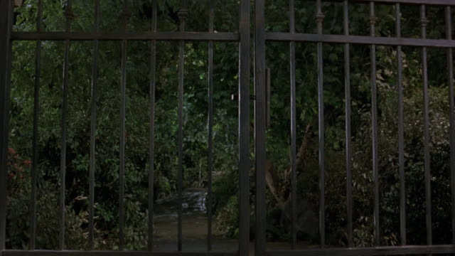 """high angle down of dirt road. pans up to front gate entrance of """"central park"""" see bushes and trees behind fence. pans up to ball-shaped lights hanging from thatched ceiling of gazebo. - gazebo stock videos and b-roll footage"""