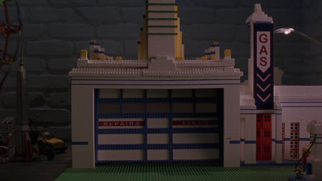 "medium angle of blue and white building made of legos. could be garage. see ""repairs"", ""tires"", and ""gas"" signs on side of lego building.  see brick wall in background. see garage door open. see red remote control convertible car parked in garage. see lig - blue convertible stock videos & royalty-free footage"