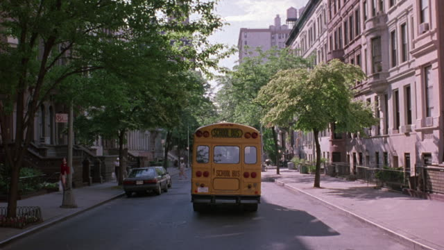 medium angle of reflection of high rise building on rear window of school bus. yellow school bus moves away from pov down side street with apartment buildings on sides. - 1999 stock videos & royalty-free footage