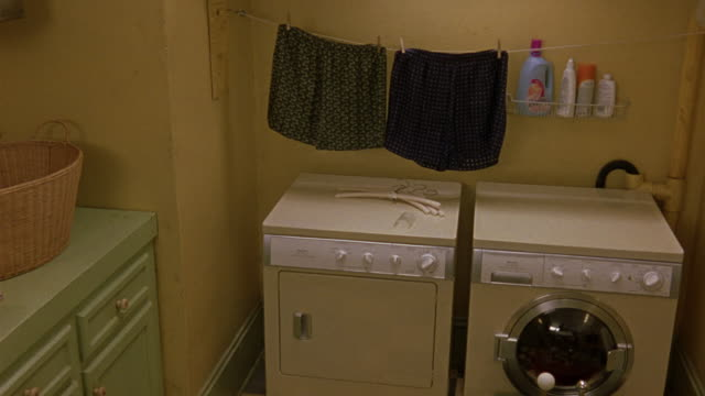 MEDIUM ANGLE OF LAUNDRY ROOM. SEE YELLOW WASHER AND DRYER. SEE LAUNDRY LINE WITH TWO PAIRS OF BOXER SHORTS, UNDERWEAR HANGING OVER WASHER AND DRYER. SEE GREEN CABINETS TO FRAME LEFT. CAMERA SLOWLY MOVES OUT OF FOCUS.