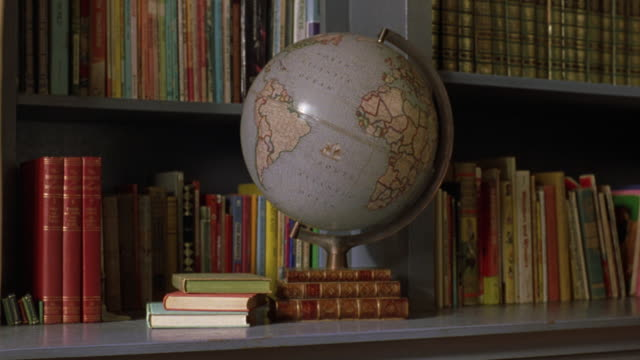 stockvideo's en b-roll-footage met medium angle of blue bookshelves lined with books. see large globe propped on shelf in front of shelves. could be in library. - shelf