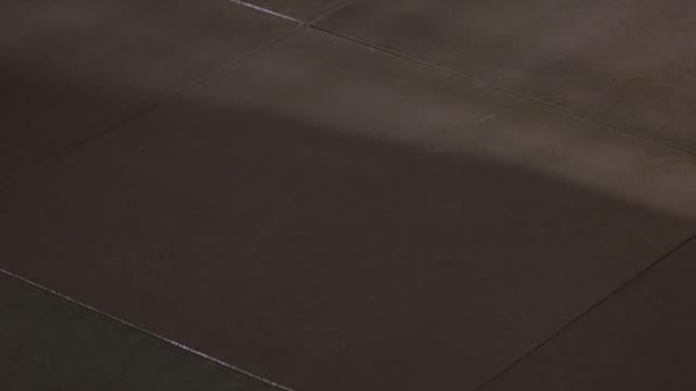 medium angle of cement floor. see leather baseball roll across floor. - コンクリート点の映像素材/bロール