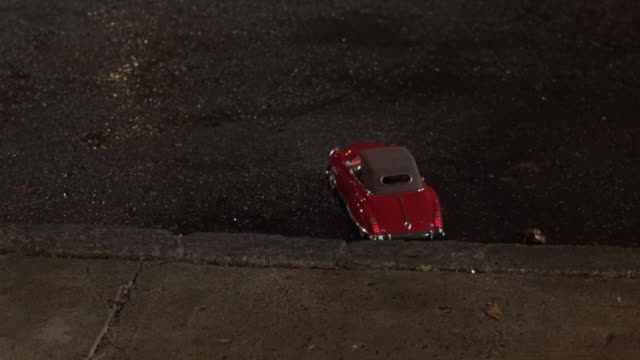 medium angle of red remote control convertible car. see car move away from pov and drive across street. see wall with vines on front and benches. could be at park. see pedestrians walk on sidewalk. see trees in background behind wall. - ラジコン点の映像素材/bロール