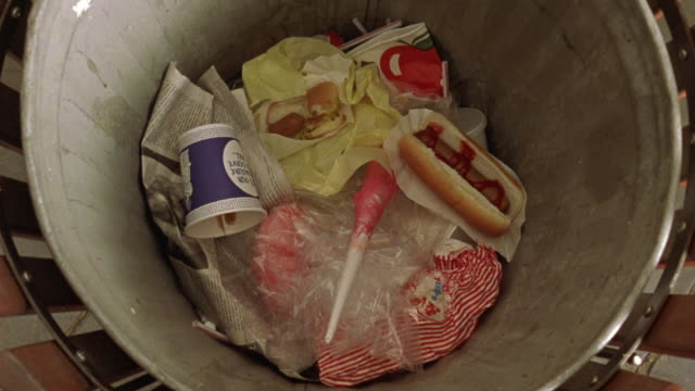 CLOSE ANGLE OF GARBAGE CAN. POV LOOKING DOWN INTO CAN. SEE CUPS, NAPKINS, HOT DOG WITH KETCHUP. SEE HOT DOG TOSSED DOWN INTO CAN.