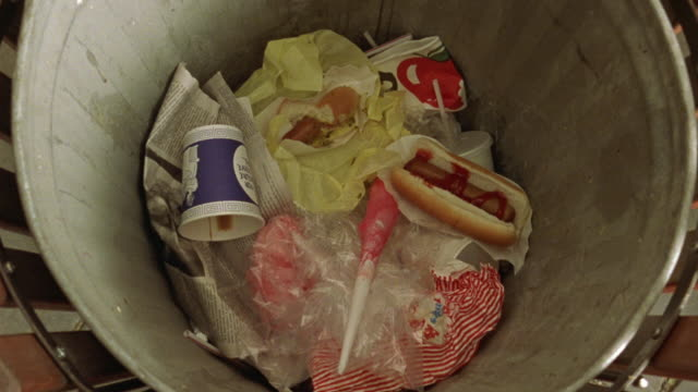 vídeos de stock e filmes b-roll de close angle of garbage can. pov looking down into can. see cups, napkins, hot dog with ketchup. see two hot dogs tossed down into can. - lixeira