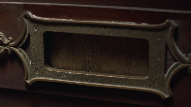 close angle of metal mail slot on wooden door. pov zooms back as slot opens to show outside. see slot close. - letterbox stock videos & royalty-free footage