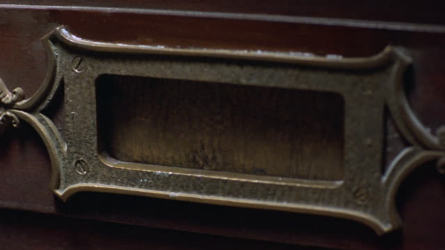 close angle of metal mail slot on wooden door. pov zooms back as slot opens to show outside. see slot close. - letterbox stock videos and b-roll footage