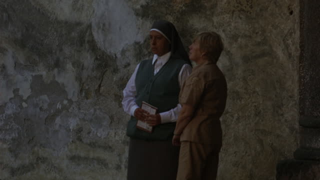 vídeos de stock, filmes e b-roll de medium angle of woman or tourist standing with nun outside stone building. both distracted and looking off screen. - nun