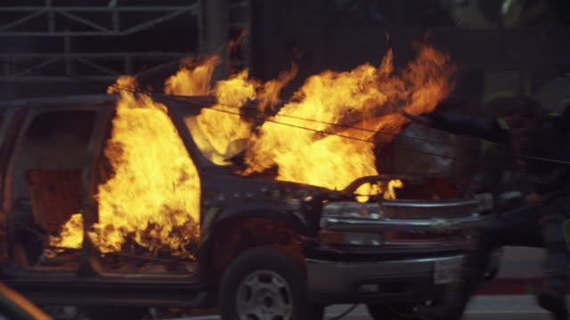 pan left to right of gunman or man shooting from broken glass doors of building to police cars with flashing lights or bizbars and car fire or chevrolet suburban suv in flames. bullet holes visible. gunfire. gunshots. stuntman thrown back from explosion a - police car stock videos & royalty-free footage