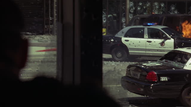 MEDIUM ANGLE OF POV OF GUNMAN OF POLICE OFFICER OR SWAT TEAM SHOOTING GUN. POLICE CAR WITH FLASHING LIGHTS OR BIZBARS, CAR FIRE, FLAMES, AND MULTI-STORY OFFICE BUILDING IN BACKGROUND. POLICE ACTION OR POLICE STAND-OFF. GUNSHOTS. GUNFIRE. COULD BE FOR ATTA