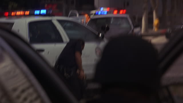 hand held of police officers or swat team shooting guns towards multi-story office building or bank from behind police cars with flashing lights or bizbars. smoke, debris, and broken glass visible. injured or wounded officer in background. could be for ho - 銃点の映像素材/bロール