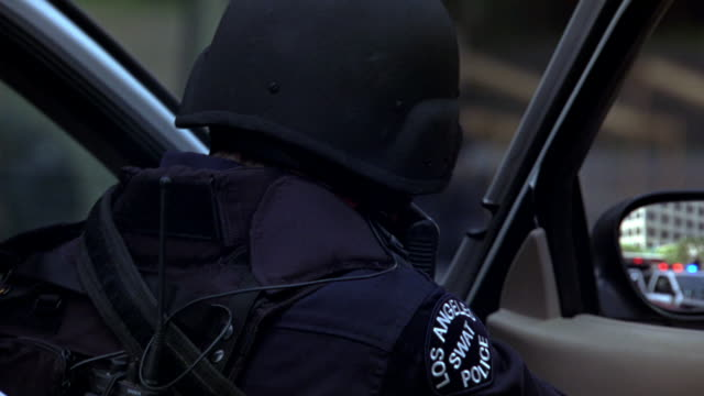 """hand held of police officers or swat team with guns or rifles behind police cars with flashing lights or bizbars. swat team surround multi-story office building. """"los angeles swat police"""" badge visible. could be for attack, police action, police stand-off - 銃点の映像素材/bロール"""