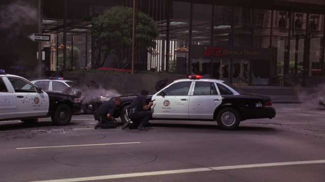 wide angle of police officers or swat team with guns and rifles kneeling behind police cars with flashing lights or bizbars. multi-story office building or bank in background. bullet holes in police cars visible. could be for police action or police stand - 銃点の映像素材/bロール