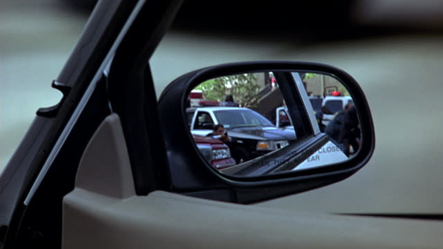 close angle from rear view mirror pov of police officers or swat team shooting guns behind police cars with flashing lights or bizbars. could be for hold up, attack, police action, or police stand-off. - armed police forces stock videos & royalty-free footage