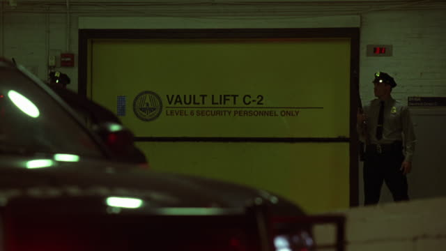 stockvideo's en b-roll-footage met medium angle of police officers or security guards in federal reserve bank warehouse or garage. uniforms. officers holds shotguns and stand near vault lifts or elevators. flashing lights out of focus in fg. - jachtgeweer