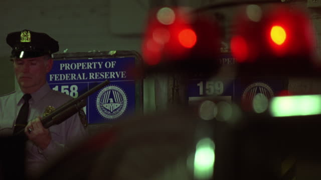 medium angle of police officers or security guards in federal reserve bank warehouse or garage. officer holds shotgun. flashing lights out of focus in fg. - bank stock-videos und b-roll-filmmaterial