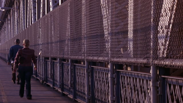 vídeos de stock e filmes b-roll de close angle of chain link fence and iron girders or rails on manhattan bridge bike path or walkway. pedestrians walk down path or walkway. - chain bridge suspension bridge