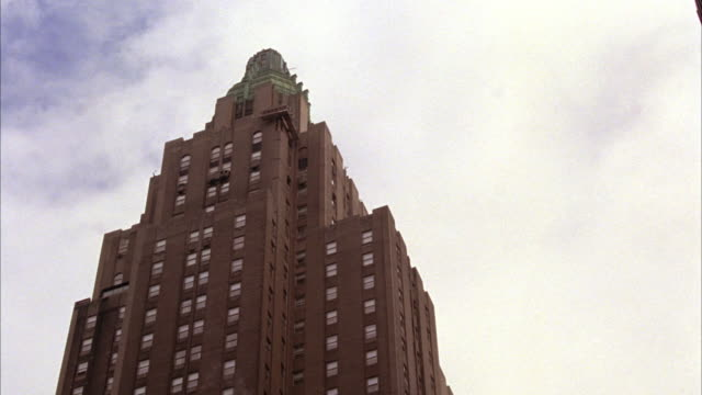 PAN DOWN FROM TOP OF WALDORF ASTORIA HOTEL IN NEW YORK TOWARDS STREET.  BROWNSTONE SKYSCRAPER IN NEW YORK CITY.
