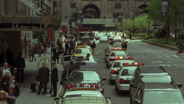 wide angle of park avenue in new york in front of waldorf astoria. police cars and cars and taxis parked in front of sidewalk. bystanders and tourists waiting on sidewalk. see tourist bus in bg. - ウォルドルフ・アストリア点の映像素材/bロール