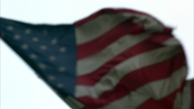 medium angle of american flag on flagpole outside building waving in wind. building is waldorf astoria hotel on park avenue in new york. handheld effect. - waldorf astoria stock videos and b-roll footage