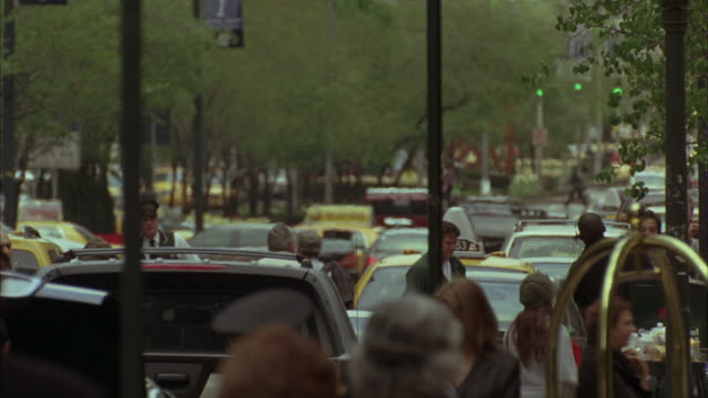 wide angle of park avenue in new york in front of waldorf astoria off-screen. tourists and bystanders on sidewalk with luggage. planning to check in or check out. taxis on street in bg. - ウォルドルフ・アストリア点の映像素材/bロール