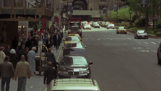 wide angle of park avenue in new york in front of waldorf astoria. cars and police cars and taxis in traffic. bystanders and tourists stand in front of hotel. as two men cross the street police cars rush up and park with bizbars going and pull out guns to - ウォルドルフ・アストリア点の映像素材/bロール
