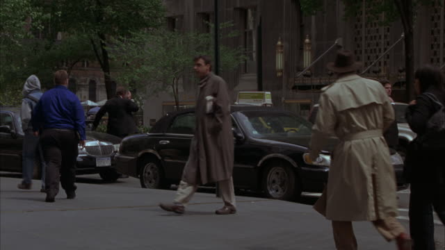 wide angle of pedestrians on new york street corner. park avenue  across from waldorf astoria hotel. see traffic and police cars with bizbars pull up in front of hotel across the street, as if starting a police action. police officers get out of cars and - ウォルドルフ・アストリア点の映像素材/bロール