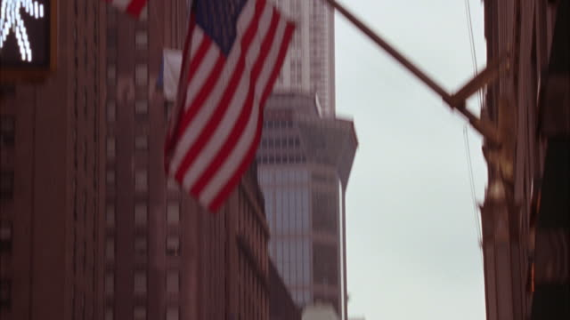wide angle of american flag blowing slowly in wind on flagpole in front of building. building is waldorf astoria. see chrysler building in bg. new york skyline. pan down to street level of side entrance with awning with name of hotel on side in script. by - ウォルドルフ・アストリア点の映像素材/bロール