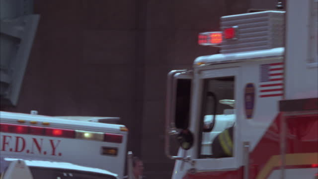 tracking shot of fdny fire engine driving down new york street with sirens on.  past other emergency vehicles and police cars and police officers parked along street. bizbars and flashing lights. - fire department of the city of new york stock-videos und b-roll-filmmaterial