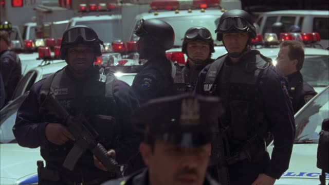 wide angle of fdny and police officers and swat team members on street surrounded by emergency vehicles. officers wait around with guns or rifles drawn. see bizbars and flashing lights in bg. - fire department of the city of new york stock-videos und b-roll-filmmaterial