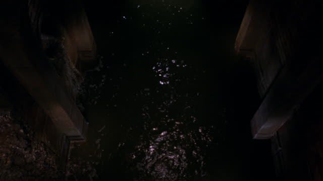 HIGH ANGLE DOWN OF SEWER OR MOAT. SEE WATER RUNNING AWAY FROM POV. SEE STONE WALLS ON EITHER SIDE OF WATER. POV COULD BE FROM BALCONY OR BRIDGE OVERLOOKING WATER. SEE ROUND BALL GET THROWN INTO WATER. SEE WATER TRICKLE DOWN SIDE OF WALL.