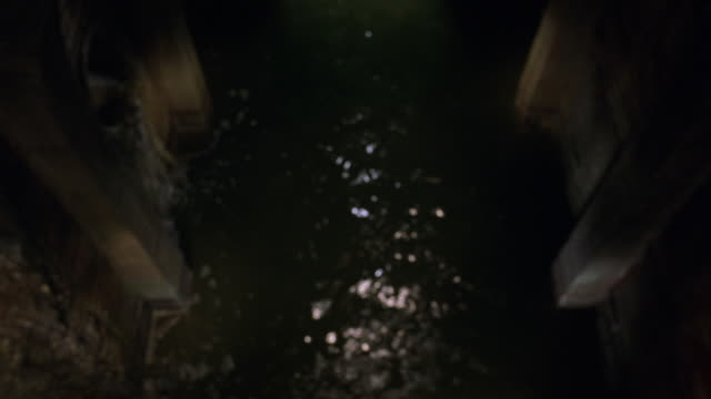 high angle down of sewer or moat. see water running away from pov. see stone walls on either side of water. pov could be from balcony or bridge overlooking water. see water trickle down side of wall. see red remote control convertible car drive over edge - ラジコン点の映像素材/bロール