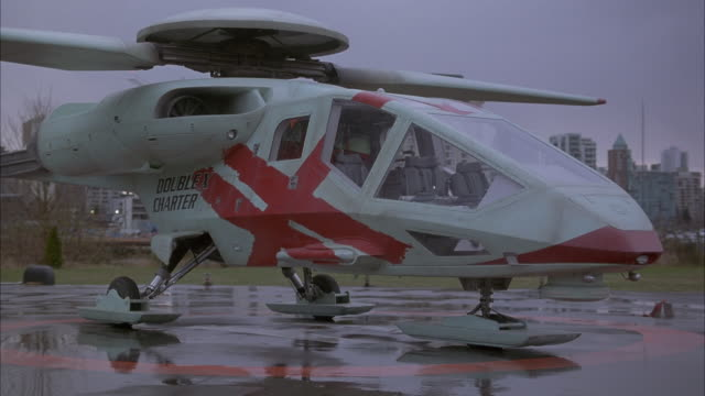"MEDIUM ANGLE OF FUTURISTIC WHITE HELICOPTER WITH PAINTED RED SLASHES ACROSS ITS SIDE. SEE RAIN-SLICKED LANDING PADS ON PAVEMENT. SKIES ARE OVERCAST. SEE ""DOUBLE A CHARTER"" WRITTEN ACROSS SIDE OF EMPTY HELICOPTER. SEE BUILDINGS OF CITY IN THE BACKGROUND."