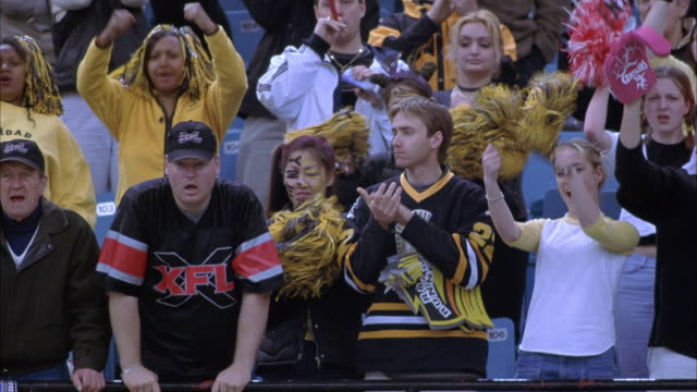medium angle of crowd in stadium bleachers at football game. see members of crowd dressed in team colors waving arms in the air to cheer on their football team. faces of people are painted to show spirit. see yellow pompoms being waved. - game show stock videos & royalty-free footage