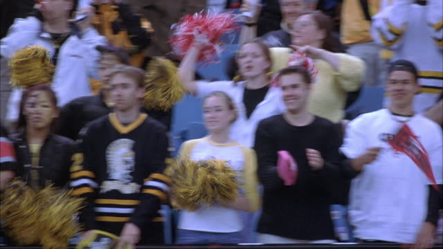medium angle of crowd in stadium bleachers at football game. see members of crowd dressed in team colors waving arms in the air to cheer on their football team. faces of people are painted to show spirit. see yellow pompoms being waved. - game show stock videos and b-roll footage