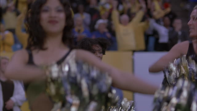 medium angle of gold and black spandex-clad cheerleaders performing routine. see her sway her hips back and forth dancing while waving pompoms to cheer on football team at game. see green grass of football field. crowd is in the background. - cheerleader stock videos and b-roll footage