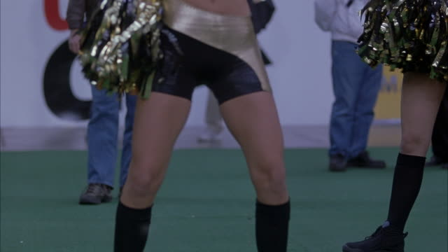 medium angle of gold and black spandex-clad hips of cheerleader. see her sway her hips back and forth dancing while waving pompoms to cheer on football team at game. see green grass of football field. - spandex stock videos & royalty-free footage