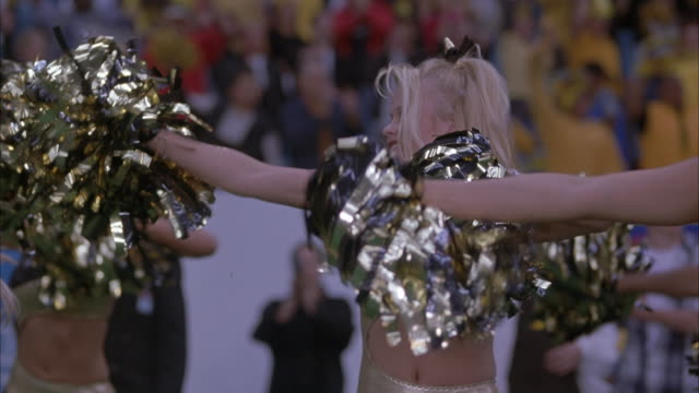 MEDIUM ANGLE OF GOLD AND BLACK SPANDEX-CLAD CHEERLEADERS PERFORMING ROUTINE. SEE HER SWAY HER HIPS BACK AND FORTH DANCING WHILE WAVING POMPOMS TO CHEER ON FOOTBALL TEAM AT GAME. SEE GREEN GRASS OF FOOTBALL FIELD. CROWD IS IN THE BACKGROUND.
