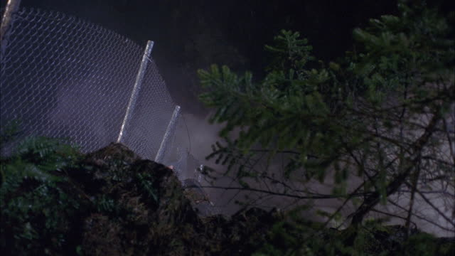 up angle of chain link fence on edge of cliff or road. see pine tree branches in foreground. see white smoke blowing toward left of screen. camera pans upwards to see fence fall over. - chainlink fence stock videos and b-roll footage