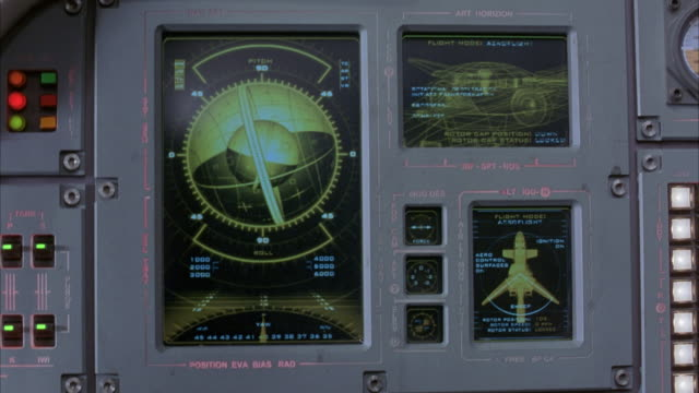CLOSE ANGLE OF INSTRUMENT PANEL, COULD BE CONTROLS FOR A MISSILE,  ROCKET GYROSCOPE. MAY BE LOCATED ON NAVY SHIP, OR MILITARY AIRPLANE.  COMPUTER GRAPHICS, MONITORS. SHAKEY CAMERA. BLUE SCREEN IN BACKGROUND.