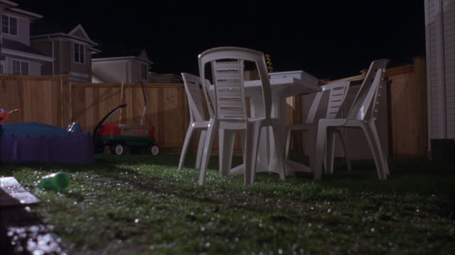 MEDIUM ANGLE OF WHITE PLASTIC PATIO TABLE SET ON GRASS. SEE TRACT HOUSES IN BACKGROUND. COULD BE BACKYARD OF HOME. SEE 1950'S ERA VINTAGE RED CADILLAC DRIVE FORWARD AND RUN OVER PLASTIC TABLE SET. SEE CAR CRASH THROUGH WOODEN FENCE IN BACKGROUND. SEE DAMA