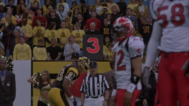 "STEADICAM FAST MOTION OR TIME LAPSE SHOT OF PROFESSIONAL OR COLLEGE FOOTBALL PLAYERS ON FOOTBALL FIELD. SEE REFEREE AT SCRIMMAGE LINE. SEE CROWD OF SPECTATORS IN STANDS WEARING YELLOW AND BLACK SHIRTS THAT SPELL OUT ""ROAD RUNNER"". PLAYERS LINE UP FOR NEXT"